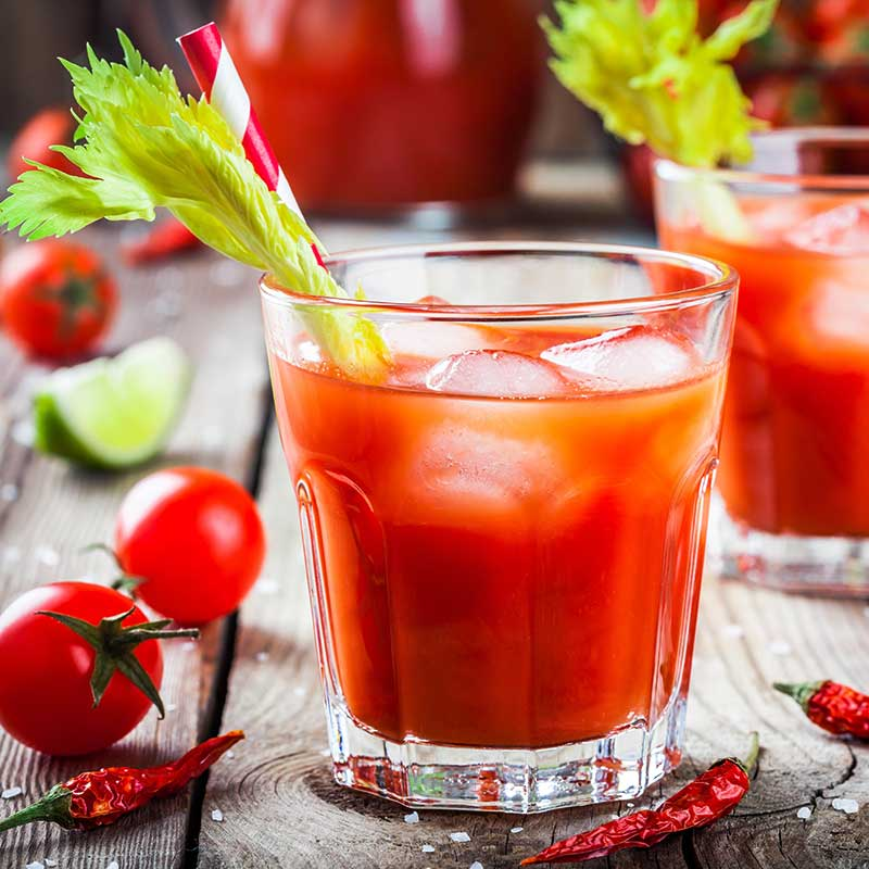 Kimo Bloody Maria in a clear glass with celery garnish, on a table with cherry tomatoes and chiles