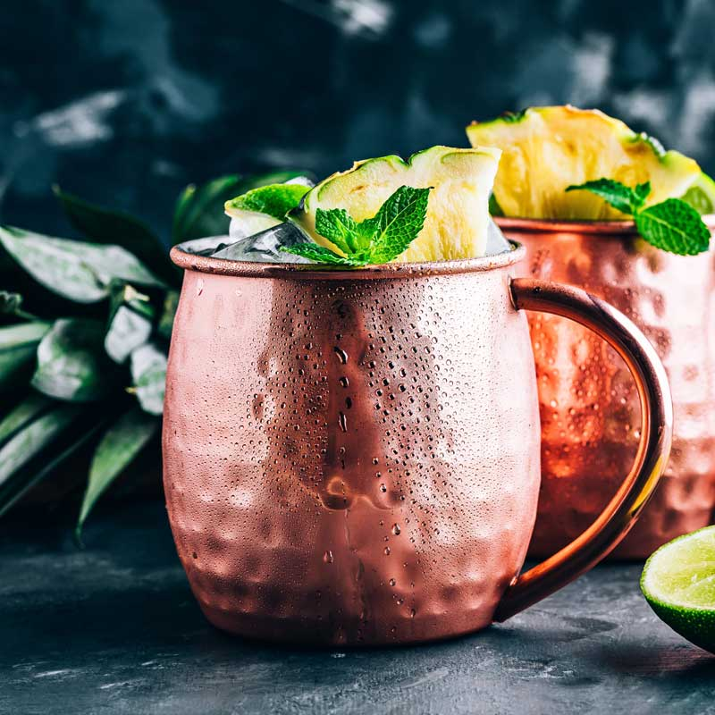 Pineapple Mezcal Mule in a copper mug surrounded by pineapple and limes